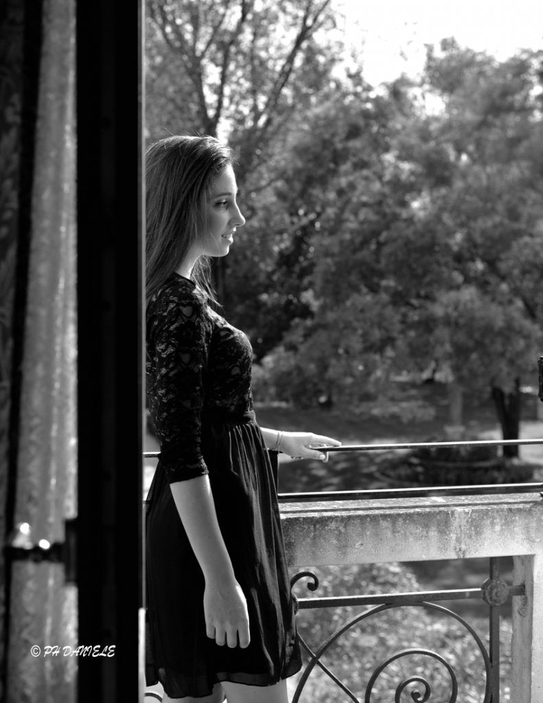 Elena on a balcony, lost in her thoughts. The angelic woman