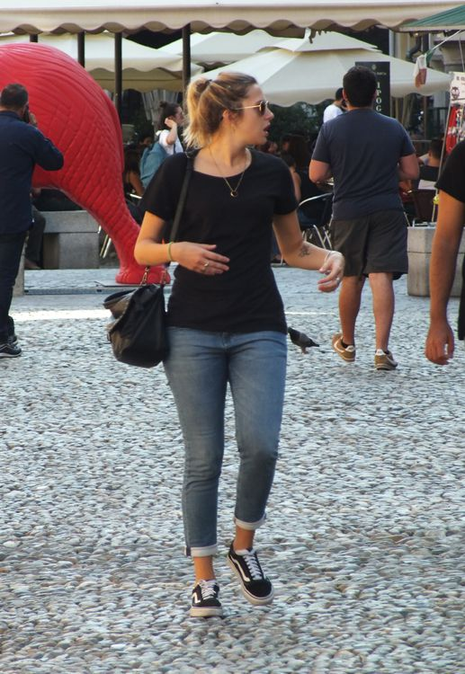 Italian girl wearing a black t-shirt, cuffed jeans and sneakers, carries a black bag