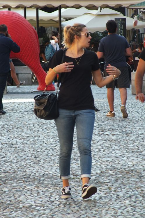 Italian girl wearing a black T-shirt, cuffed jeans and sneakers