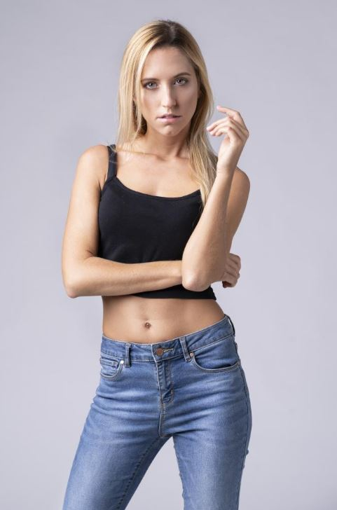 Giulia's outfit: denim trousers and black top. Italian blond model posing in Italy